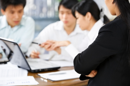Female boss watching her employees working in the office photo