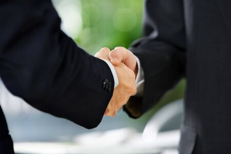 welcoming: close up image of handshake between two businessmen. East Asian skin tone
