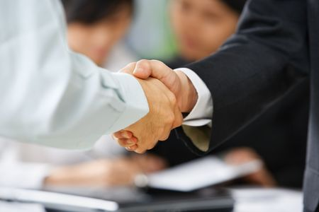 Handshake between employee and boss to ilustrate he is being accepted in the team photo