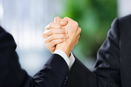 cohesive: Two businessman grasp each other hand, East Asian skin tone.
