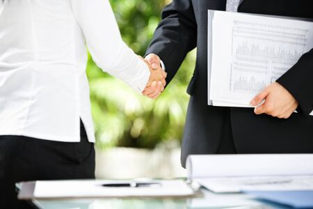 Handshake between businessman and businesswoman in a meeting photo