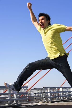 ps: Young man jumping freely in bridge area. *** PS: showing blur movement even in face area*** Stock Photo