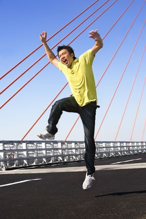 wierd: Young man jump with wierd expression in bridge area *** PS: showing blur movement even in face area***