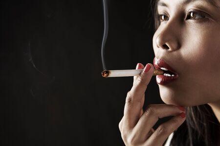 cigar smoking woman: Woman smoking on dark area Stock Photo