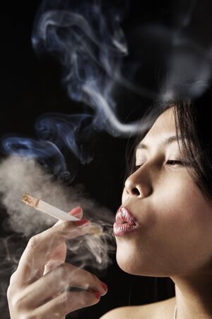 Female inhale smoke from cigarette on dark area photo