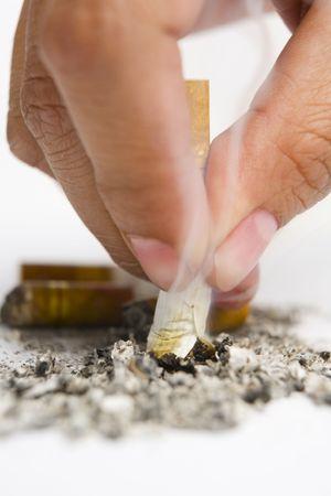 Fingers turn off the cigarrete on white ashtray photo