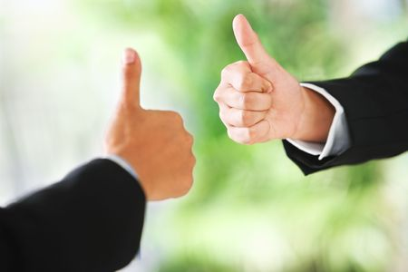 People raise thumbs up in line with green environment background. DIfferent skin tones and shallow depth of field Stock Photo