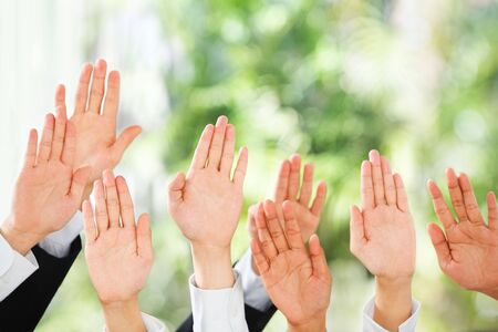 raise hand: People raise their hands up to be picked up or to bid in an auction over green background