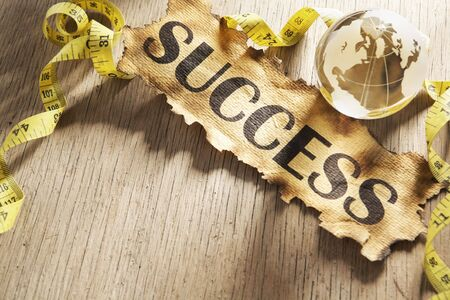 Measurement global success concept by using tape measuring around paper with word success printed on it and a glass globe Stock Photo - 5557697