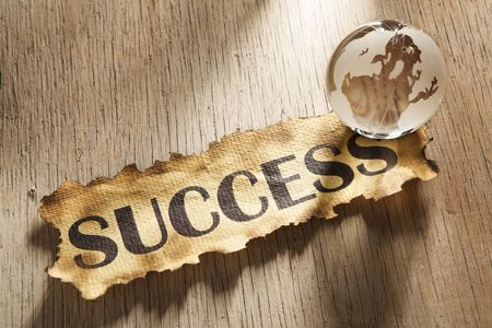 Global success concept made from word success printed on burnt paper and a glass globe, and using hard lighting Stock Photo - 5557694