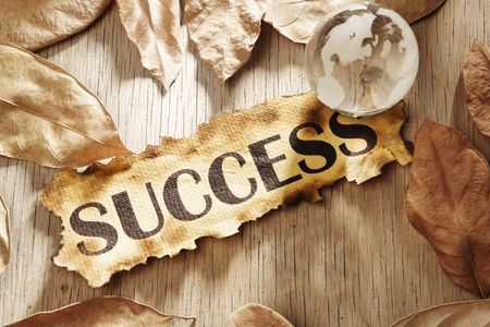 Global success concept made from word success printed on burnt paper and a glass globe with dry leaves scattered around, and using hard lighting Stock Photo - 5557690