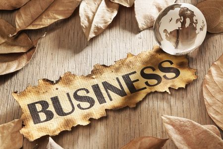 Global business concept using printed word on burnt paper along with compass and golden key, surrounded by dry leaf Stock Photo - 5557693