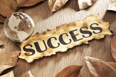 Global success concept using printed word on burnt paper along with compass and golden key, surrounded by dry leaf Stock Photo - 5557675