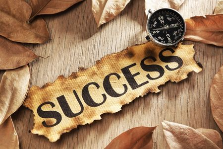 Guidance to success concept using printed word on burnt paper along with compass, surrounded by dry leaf Stock Photo - 5557705