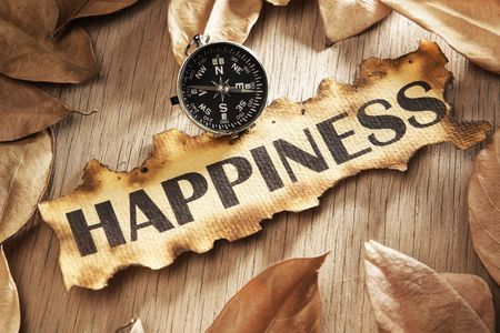 Guidance and key to happiness concept using printed word on burnt paper along with compass, surrounded by dry leaf Stock Photo - 5557702