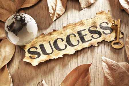 Key to global success concept using printed word on burnt paper along with compass and golden key, surrounded by dry leaf photo