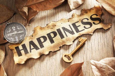 Guidance and key to happiness concept using printed word on burnt paper along with compass and golden key, surrounded by dry leaf photo