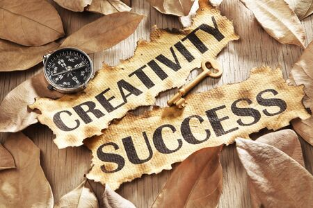 Creativity is key to success concept using words printed on burnt paper and related objects, surrounded with dry leaf Stock Photo - 5557699