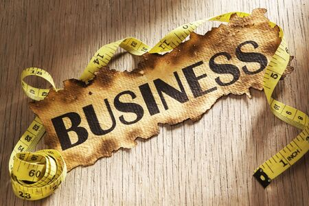 Measurement for business concept by using tape measuring around burnt paper with word business printed on it. Stock Photo - 5557725