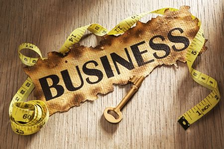 Measuring business concept using burnt paper with word businessprinted on it and golden key surrounded by measuring tape photo