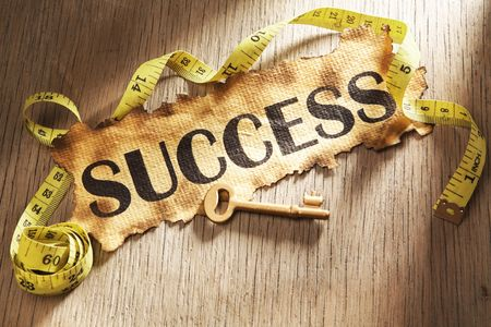 measurement: Measuring success concept using burnt paper with word success printed on it and golden key surrounded by measuring tape Stock Photo