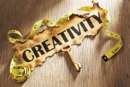 Measuring creativity concept using burnt paper with word creativity printed on it and golden key surrounded by measuring tape photo