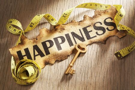 Measuring happiness concept using burnt paper with word happiness printed on it and golden key surrounded by measuring tape photo