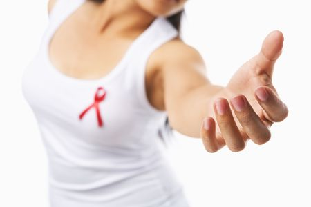 Woman giving her hand to give support for AIDS cause, using red ribbon badge on her chest. PS: you can change the ribbon color to pink for breast cancer support cause as both using the same symbol Stock Photo - 5557598