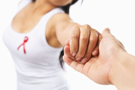 Woman holding hand to give support for AIDS cause or breast cancer, using red ribbon badge on her chest. PS: you can change the ribbon color to pink for breast cancer support cause as both using the same symbol Stock Photo - 5557591