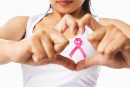 Heart framing from fingers on woman chest with pink badge to support breast cancer cause, PS: you can change the ribbon color to red to support AIDS cause as both using same symbol Stock Photo - 5557614