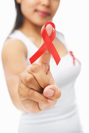 Woman pointing red ribbon badge to camera to support AIDS cause. PS: you can change the ribbon color to pink for breast cancer support as both using same symbol Stock Photo - 5557671