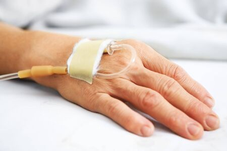 iv: Old woman hand with IV in hospitals bed