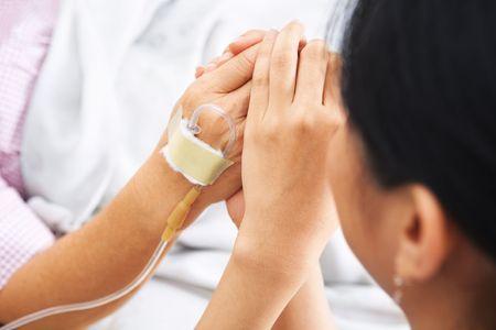 mujeres orando: Rezando por su hija de salud de la madre en el hospital, mientras sosten�a su mano, lo que inyectaba con IV
