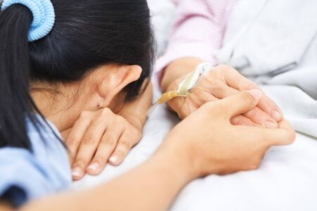 sick in bed: Daughter fall asleep waiting her mother in hospital, still holding her hand Stock Photo
