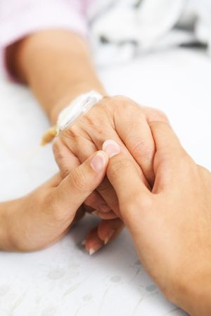 iv: Daughter holding her mother hand, that injected with IV  in hospital Stock Photo