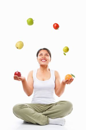 Asian woman juggling several fruits for healthy choice concept, over white background Stock Photo - 5663314