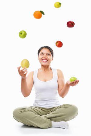 Asiatische Frau Jonglieren mehrere Früchte für gesunde Wahl Konzept, über weißen Hintergrund
