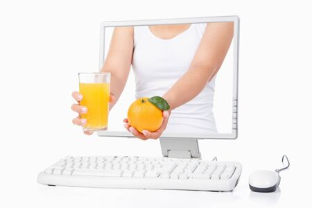 Female hand holding orange and a glass of orange juice coming out from computer screen isoalted over white background photo