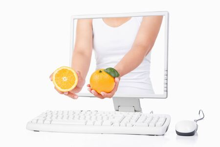 Female hand holding orange coming out from computer screen isoalted over white background photo