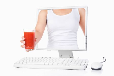 Female hand holding a glass of strawberry juice coming out from computer screen isoalted over white background photo