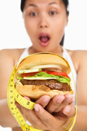 A young woman holding burger with measuring tape around, concept for diet photo