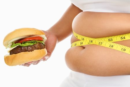 Fat stomach of a woman surrounded with measuring tape with burger over white background Stock Photo