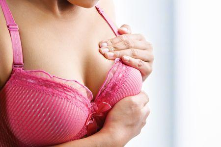 breast examination: Woman doing self breast examination using pink bra Stock Photo