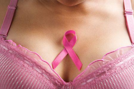 cancer de mama: lazo rosado en el pecho de la mujer para apoyar la causa de c�ncer de mama Foto de archivo