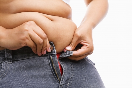 Woman trying hand to zipper her jeans, a concept for obesity issue photo