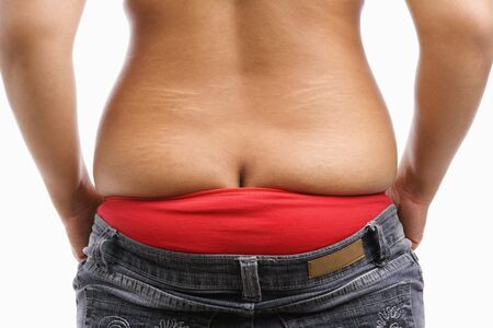 back side of fat woman trying to wear tight jeans, a concept for obesity issue Stock Photo