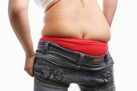 back side of fat woman trying to wear tight jeans, a concept for obesity issue photo