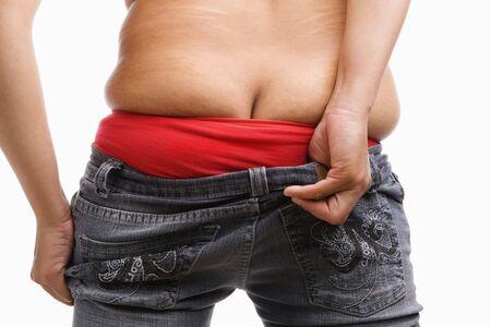 jeans apretados: parte de atr�s de la mujer gorda tratando de usar los pantalones vaqueros ajustados, un concepto para el problema de la obesidad Foto de archivo