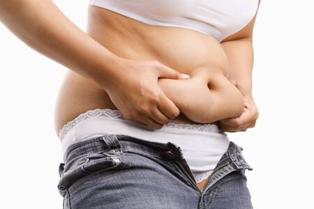 belly fat: Fat woman pinching her fat tummy, a concept for obesity issue