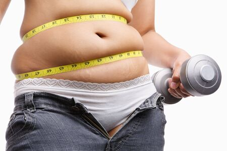 fat woman holding weight to exercise with measuring tape around her belly, a concept to fight obesity photo